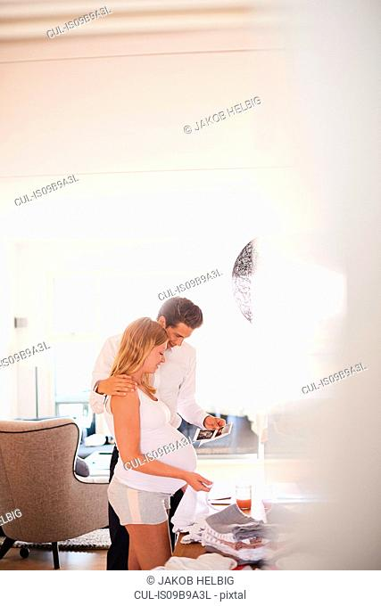 Pregnant couple looking at ultrasound pictures in living room