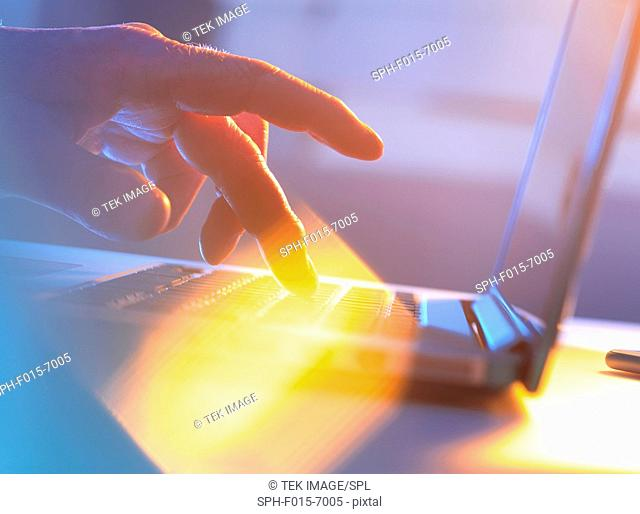 MODEL RELEASED. Close-up of silhouetted male hand typing on a laptop keyboard