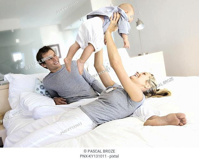 Parents and baby in bedroom, woman lifting her baby, indoors