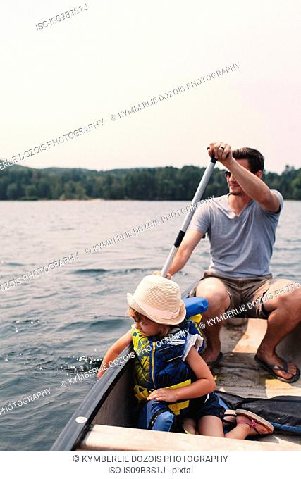 Young man and daughter rowing across lake in rowing boat