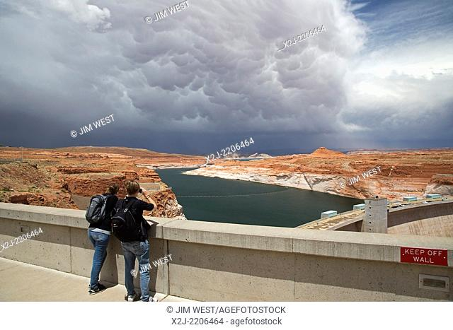Page, Arizona - Visitors to the Glen Canyon Dam watch the approach of a storm over Lake Powell. Due to years of drought, the level of the Lake Powell reservoir...