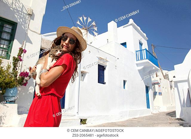 Woman posing with a local cat, Amorgos, Cyclades Islands, Greek Islands, Greece, Europe