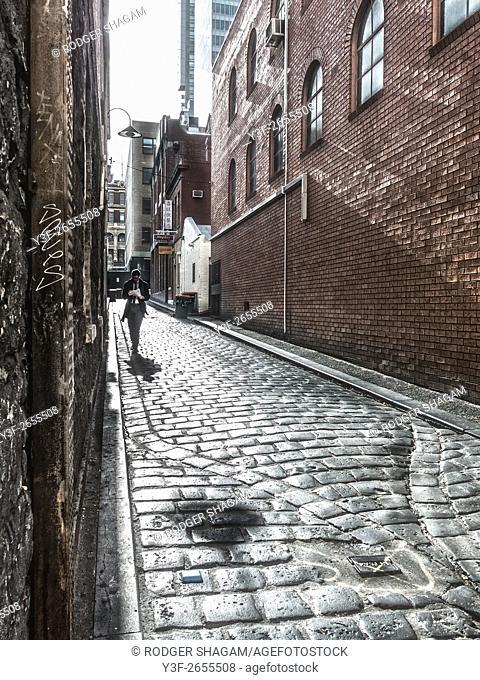a man strolls down a cobbled alley in Melbourne Australia