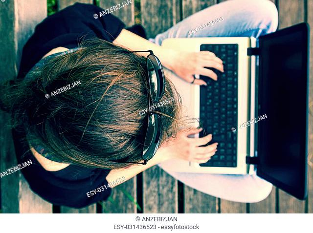 Young woman working on a laptop. View from above. Millenial generation
