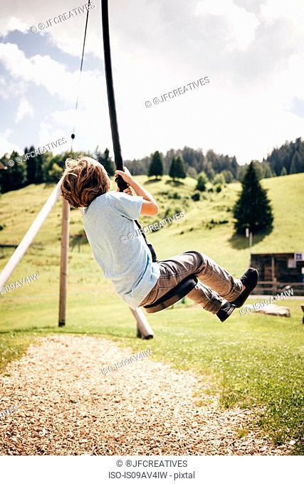 Rear view of boy sitting on zip line, Bludenz, Vorarlberg, Austria