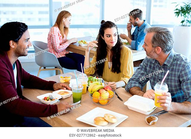Creative business team discussing while having meal