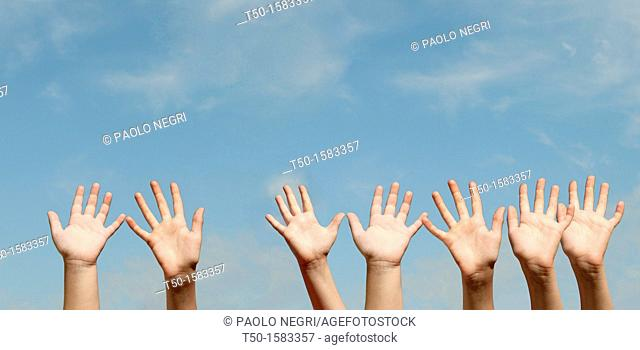 Raised hands against blue sky