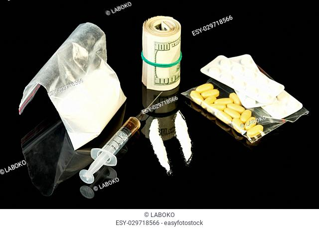 Drug syringe and heroin with pills over money