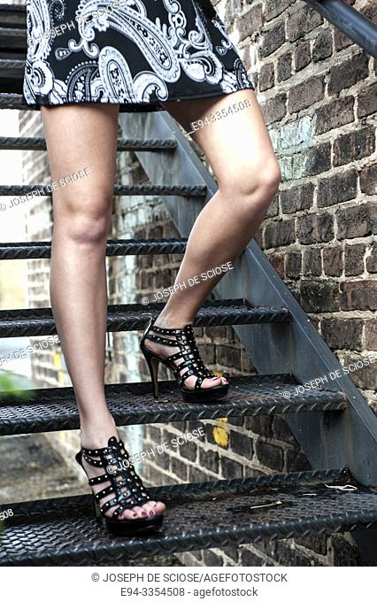 Partial view of a woman's bare legs walking down a metal stairway outdoors