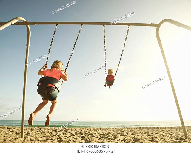 Girl (4-5) and boy (2-3) swinging on beach