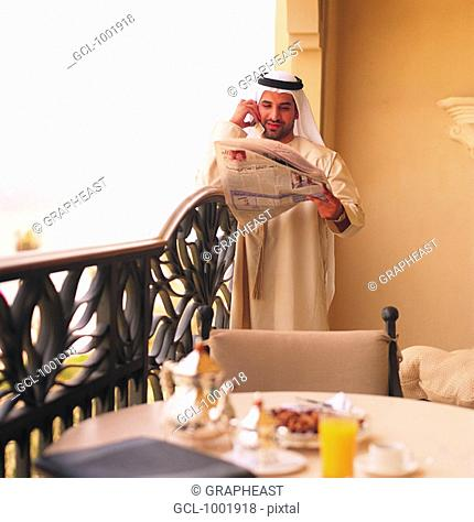 Arab businessman using mobile phone and reading newspaper