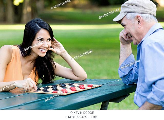 Hispanic father and daughter playing checkers