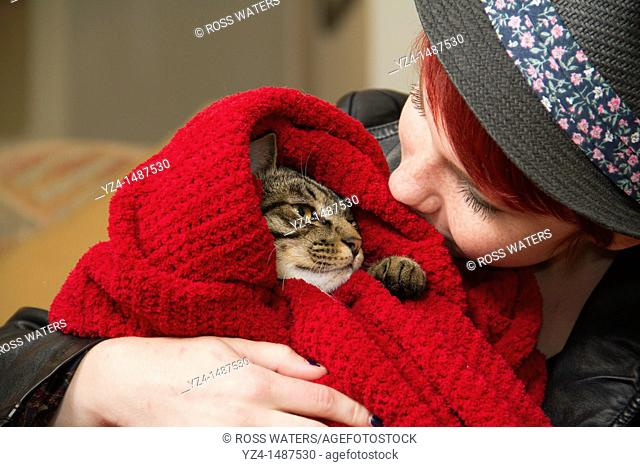 A young woman looks at her cat wrapped up in a blanket