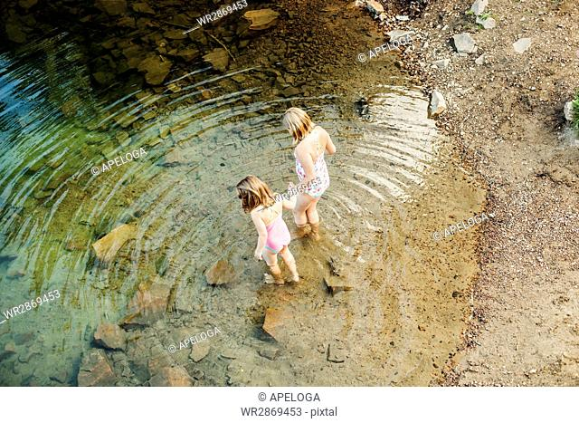 High angle view of girls holding hands while entering lake