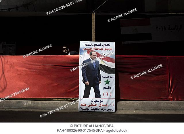 A member of Egyptian president Abdel Fattah al-Sisi's campaign stands next to a poster of the president outside a polling station on the first day of the 2018...