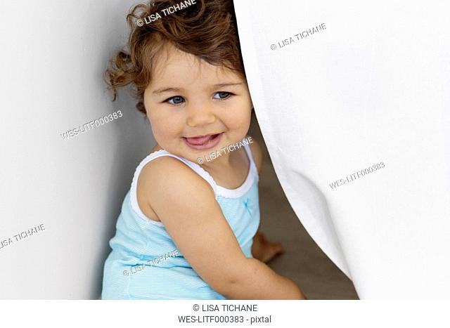 Portrait of baby girl playing hide and seek behind a white curtain with her tongue sticking out