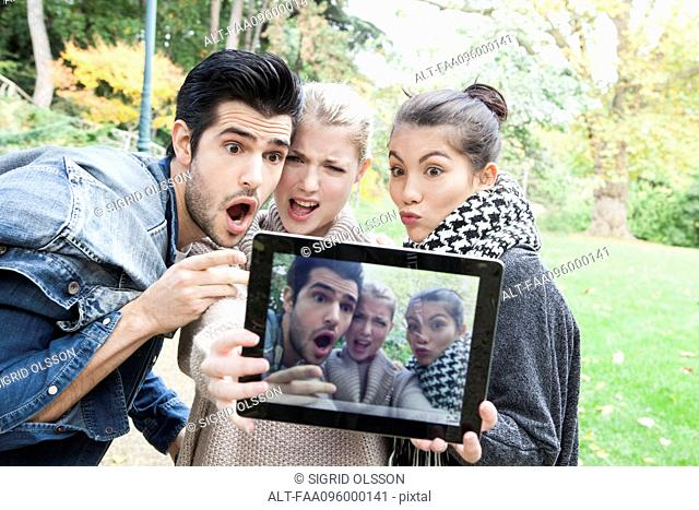 Friends photographing themselves making funny faces with digital tablet outdoors