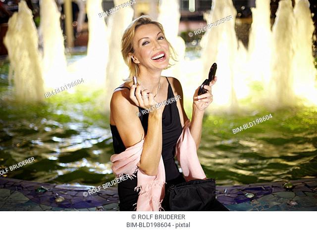 Caucasian woman putting on make up near fountain