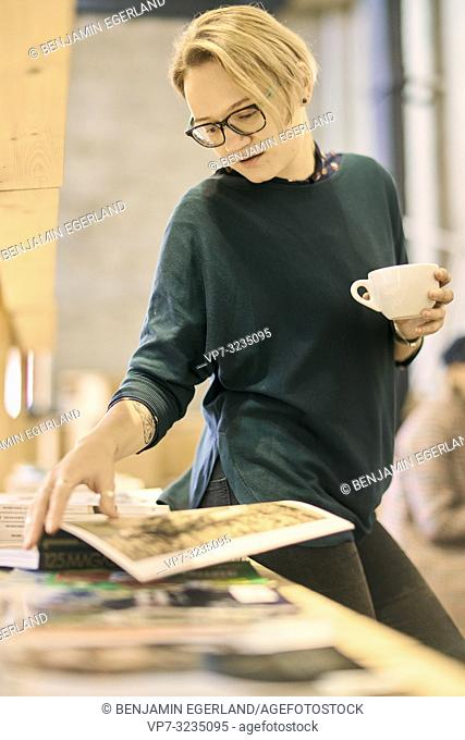 woman browsing book while holding coffee cup in book store, taking a break, in Munich, Germany