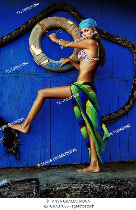 Young woman wearing bikini standing alone beside blue wooden background