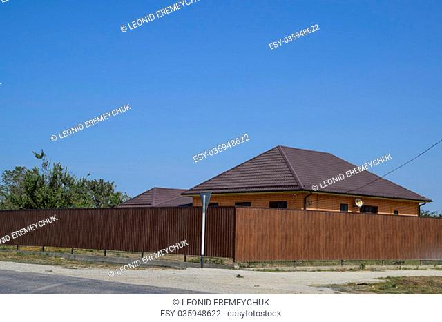 A house with a metal corrugated roof and a gauve fence made from a brown metal profile