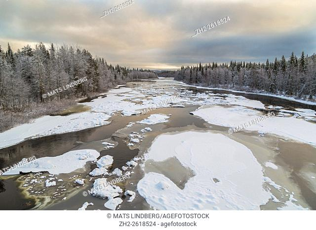 Lina river with ice floes and snow on the trees, with cloudy sky but nice colors on the clouds, Gällivare, Swedish Lapland, Sweden