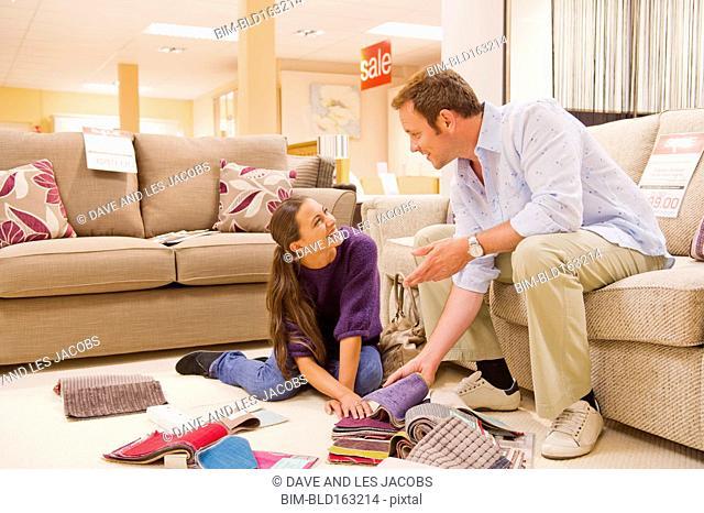 Caucasian couple examining fabric swatches in furniture store
