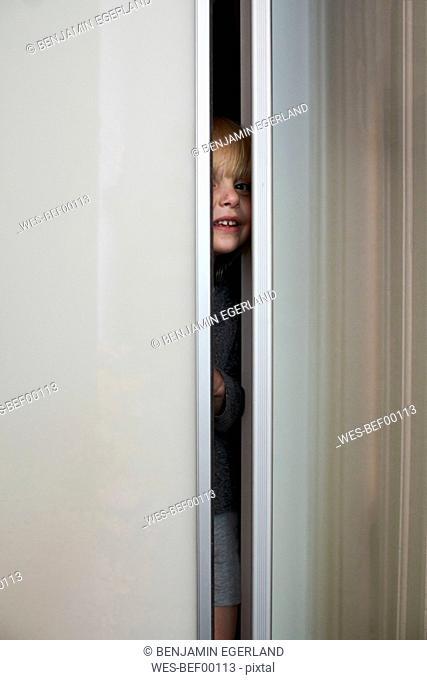 Smiling little girl hiding in wardrobe