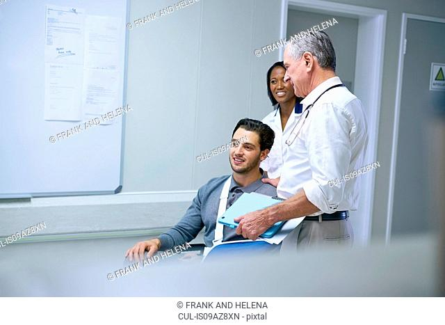 Doctor consulting with man in wheelchair with arm sling