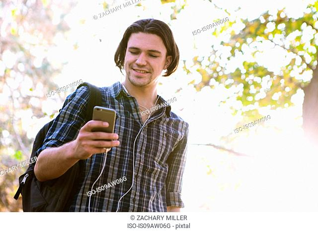 Low angle view of young man holding smartphone looking down smiling
