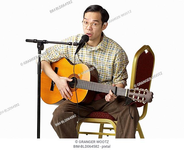 Asian man playing guitar and singing