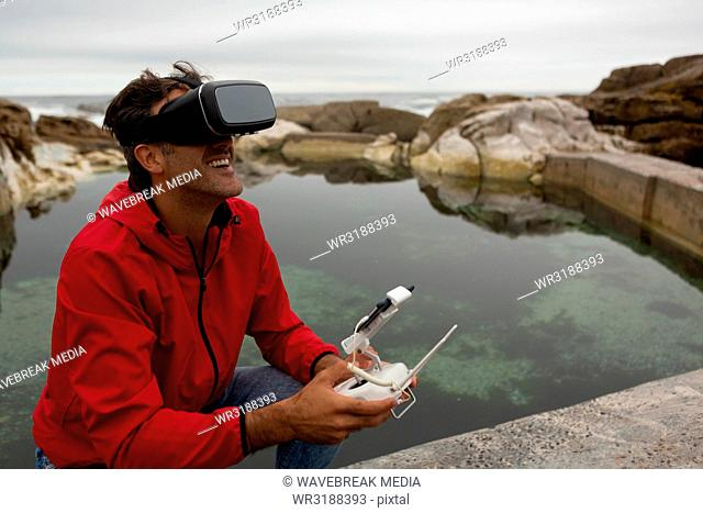 Man operating a flying drone while using virtual reality headset