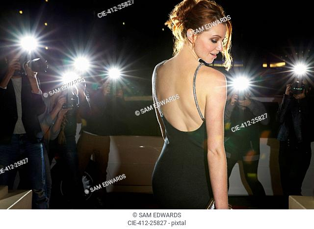 Celebrity in black dress being photographed by paparazzi photographers