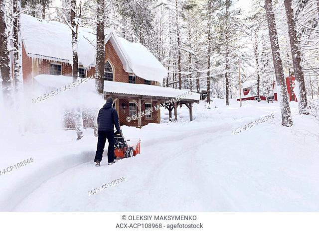 Man with a snowblower clearing a driveway in front of the house after a snow storm in Muskoka, Ontario, Canada