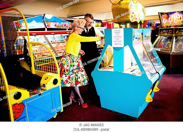 Couple enjoying themselves in amusement arcade, Bournemouth, England