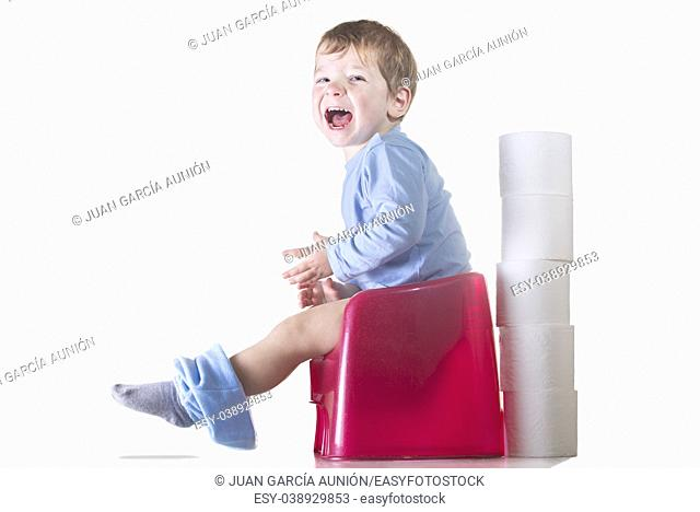 Happy baby boy sitting on chamber pot. Potty training concept