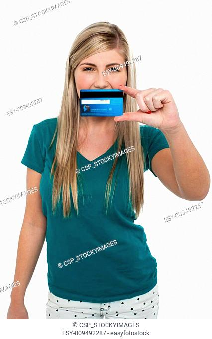 Casual teenager holding up credit card
