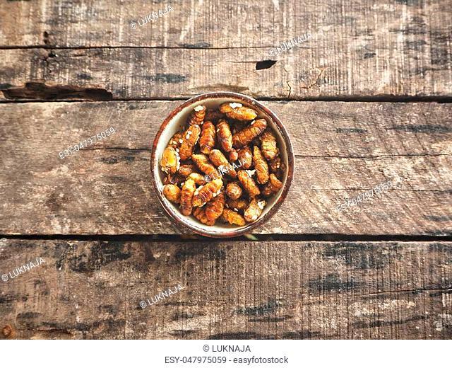 Silkworm pupae on wood background