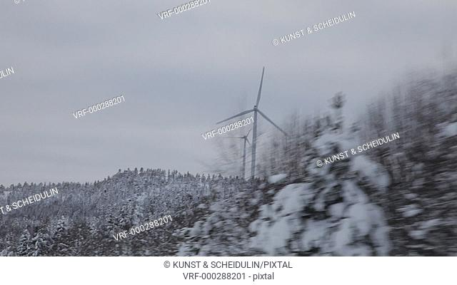 POV-shot trough the side window of a car driving past turning wind turbines on a snowy winter day. E4 near Älandsbro, Västernorrlands Län, Sweden