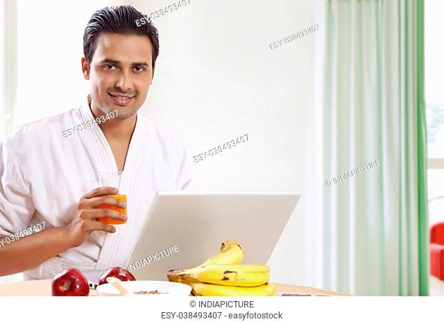Man drinking juice while using laptop at breakfast table