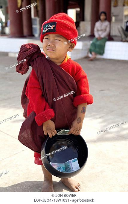 Myanmar, Mandalay, Bagan. A tiny boy in Monk's robes and red hat with a his collection bowl in Shwezigon Pagoda in Bagan in Myanmar