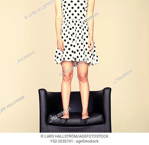 Young woman with cool attitude standing on leather armchair with bare feet.1015