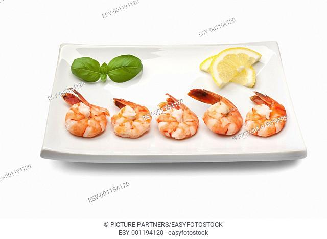 Cooked shrimps with lemon and basil leaves on a dish on white background