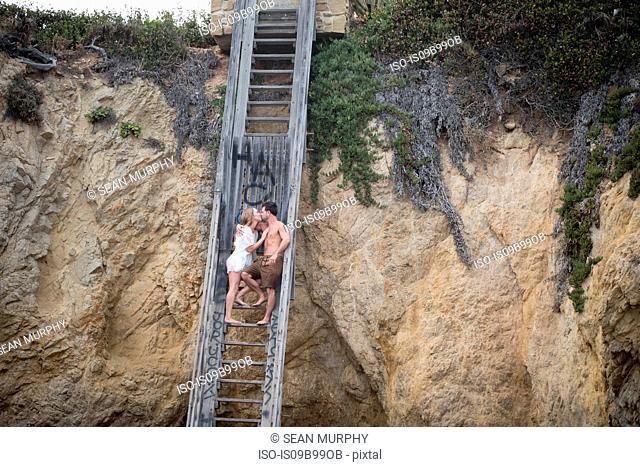 Romantic couple on stairs to beach, Malibu, California, US