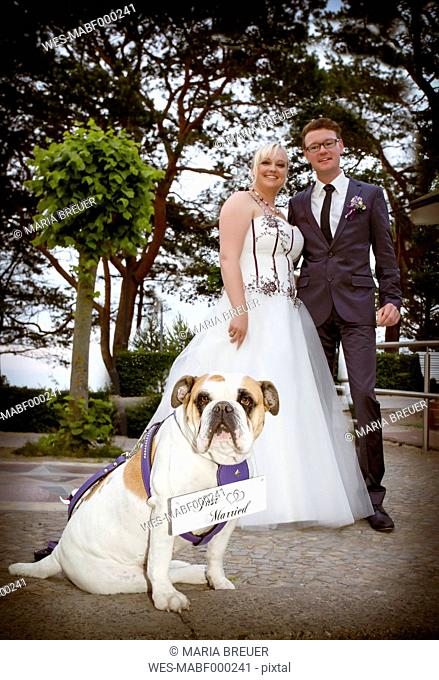 Happy bridal couple with English Bulldog in the foreground