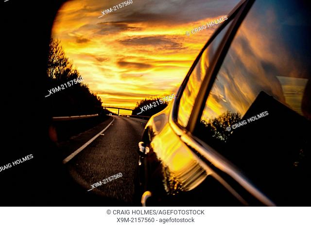 A sunset in a cars rear view wing mirror