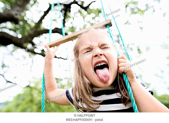 Little girl on a swing sticking out tongue