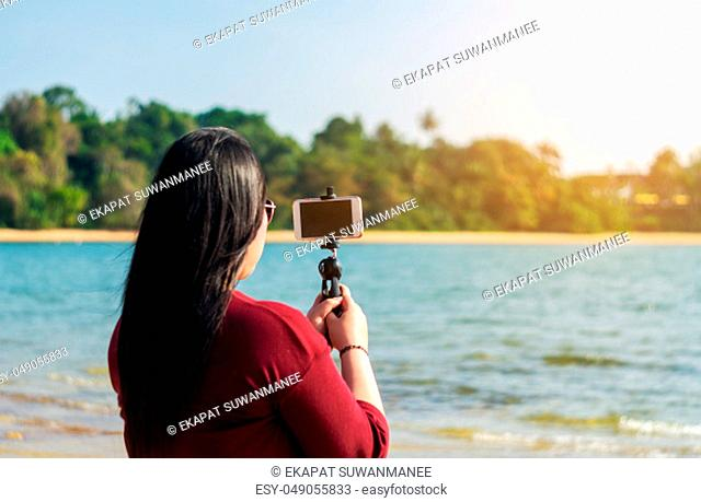Social network and photography concept, Women with smart phone mobile in seascape nature background