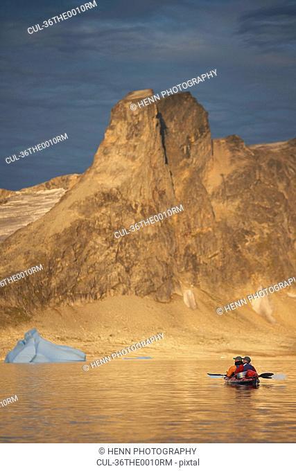 Men kayaking near dry mountains