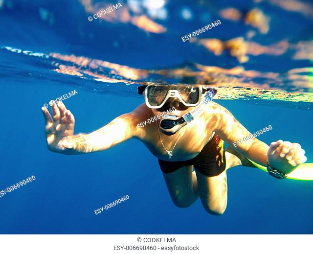 boy floats under water in the sea